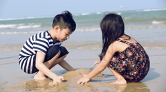 Closeup Of asian Boy And Girl Hard At Work, Building Castles In The Sand beach Stock Footage