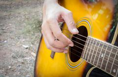 Hand playing acoustic guitar, - stock photo