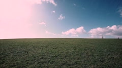 Woman jogging on  green hill with beautiful clouds above Stock Footage
