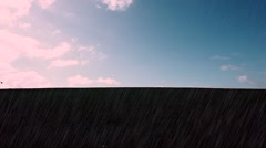 Man walking in rain on top of green hill with clouds Stock Footage
