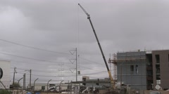 Construction crane lifts a load at a construction site Stock Footage