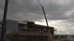 Construction workers work on industrial building - crane in background Stock Footage