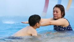 Little asian boy learning how to swimming with his mother Stock Footage