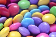Macro detail of pile of colored smarties - stock photo