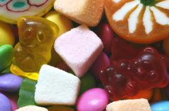 Sour jelly pink, orange and white candy on colored smarties - stock photo