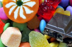 Lollipop, gummy bears, chocolate and sour candy on colored smarties - stock photo