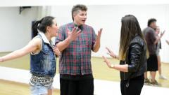 Group of three friends (dancers) argue - two women and one man - hall Stock Footage