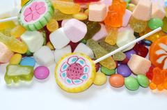Candy, lollipop, colored smarties and gummy bears background - stock photo