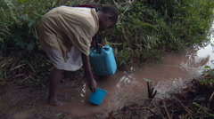 Boy scooping water in jungle Stock Footage