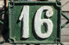 Old retro cast iron plate number 16 - stock photo