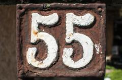 Old retro cast iron plate number 55 - stock photo