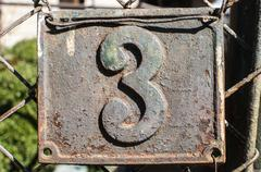 Old retro cast iron plate number 3 - stock photo
