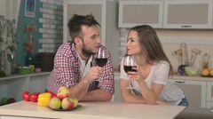 Young loving couple drinking wine in the kitchen - stock footage