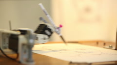 Robotic arm draws a pen on paper Stock Footage