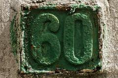 Old retro cast iron plate number 60 - stock photo