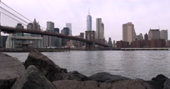 4K - View of Manhattan, Brooklyn Bridge & East River from rocky Dumbo Beach Stock Footage
