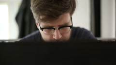 Intelligent man wearing spectacles works at the computer in studio - stock footage