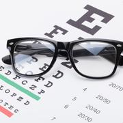 Eyesight test table and glasses over it Stock Photos