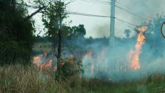 The flames of a brush fire approach a road side.60 fps. Stock Footage
