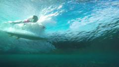 Slow motion underwater view of surfer riding wave Stock Footage
