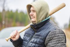 Aggressive man with a baseball bat near car Stock Photos