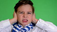 Young handsome child boy covers his ears (noise) - green screen - closeup Stock Footage