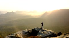 Man takes photos with smart phone on peak of rock empire. Dreamy fogy landscape - stock footage