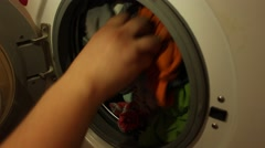 Housewife is pulling out washed laundry from the washing machine Stock Footage