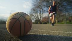 Basketball player runs and picks up the ball and dribbles to the hoop Stock Footage