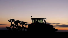 Tractor reverses plow in sunset - stock footage