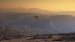 Paraglider Soaring Over The Mountains during sunset Stock Footage