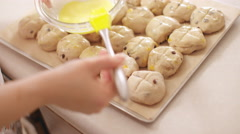 Glazing hot cross bun dough with egg yolk in slow motion 4K Stock Footage