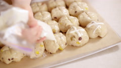 Piping crosses into hot cross bun dough in slow motion 4K Stock Footage
