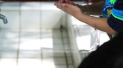 MEDIUM SHOT. Children whasing their hands in the  washbasin in the kindergarten. Stock Footage