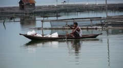 Man in canoe peddles through fish farms,Lake Maninjau,Sumatra,Indonesia Stock Footage