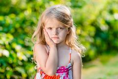 Stock Photo of Sad little girl with long blond hair suffering from toothache