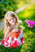 Thoughtful pretty little girl squatting and holding purple flower - stock photo