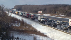 Car and truck traffic jam on highway in snow storm - stock footage