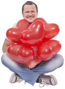 Young man sitting with red balloons on white background - stock photo
