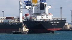 Tug boat assisting bulk carrier ship to enter port harbor Stock Footage