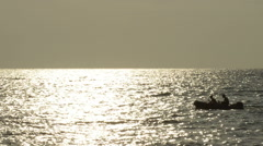 Boater speeding across the water at sunset Stock Footage