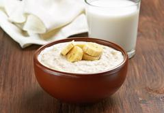 Porridge oats with banana slices and glass of milk Stock Photos