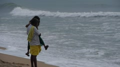 A father and daughter looks at the waves,Mahabalipuram,India Stock Footage