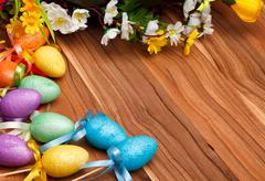 Easter flower arrangement and colorful eggs on wooden surface - stock photo