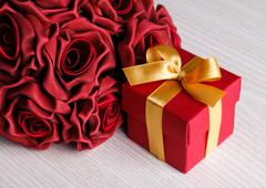 red flowers and gift box with yellow ribbon - stock photo