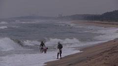 People on beach look at waves,Mahabalipuram,India Stock Footage