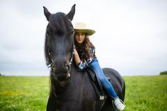 Beautiful young girl riding a horse in countryside Stock Photos