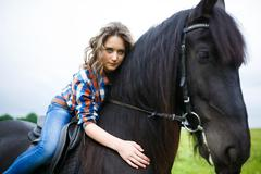 Beautiful young girl riding a horse in countryside - stock photo
