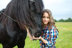 Young beautiful girl with frisian horse - stock photo