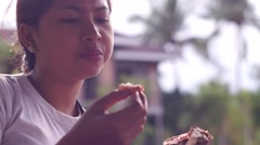Young lady eating hamburger Stock Footage
